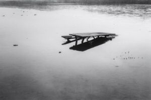 Photograph of a picnic bench in water.