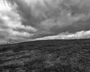 photograph of a dramatic sky under a curved ridgeline